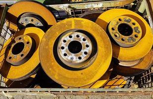 Old rusted car brake discs in the junkyard photo
