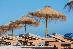hamacas y sombrillas de paja en la maravillosa isla de formentera foto