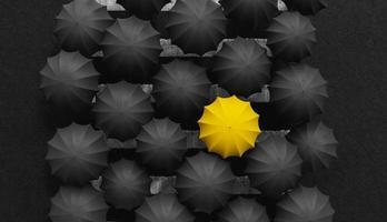 Yellow umbrella among black umbrellas, be different concept photo