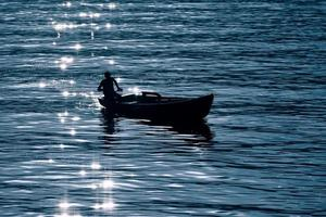 Small boat on the lake in silhouette with reflecting sunrays photo
