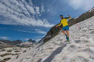 Skyrunner man corre cuesta abajo sobre la nieve entre el cielo y las montañas foto