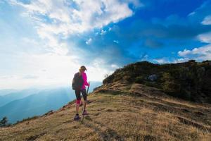 Slender woman practicing nordic walking in the mountains photo