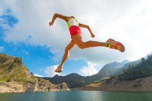 saltando chica mientras corre cerca de un lago de montaña foto