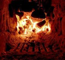 red fire from slice wood, dark grey black coals inside metal brazier photo