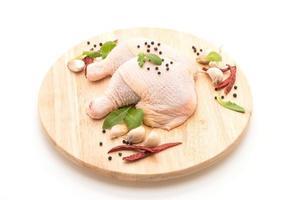 muslo de pollo sobre tablero de madera con pimientos negros, ajo y chile seco foto