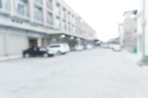 Imagen borrosa abstracta de la carretera con un coche y una casa en el pueblo de fondo foto