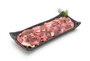 Carne de cerdo fresca en rodajas con salsa sobre fondo blanco. foto