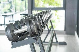 View of rows of dumbbells on a rack in a gym photo