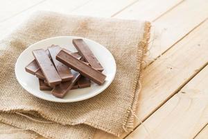 barras de chocolate sobre fondo de madera foto