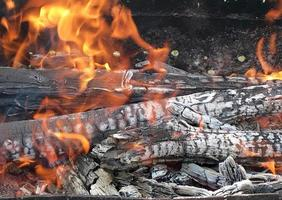 red flame from slice wood, dark grey black coals inside metal brazier. photo