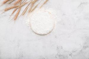 Harina de trigo en un tazón de madera sobre fondo de hormigón blanco foto