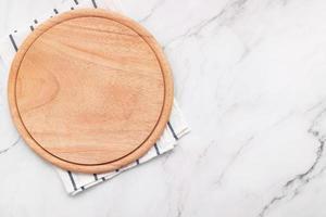 Plato de pizza de madera vacía con servilleta sobre piedra de mármol foto