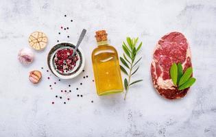 Raw Rib Eye steak set up  on white concrete background photo