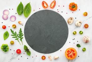 The ingredients for homemade pizza set up on white marble background photo