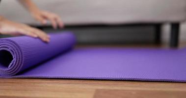 Frauenhände rollen Yogamatte auf video