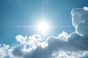Beautiful blue sky with white clouds and sun photo