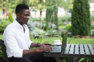 African-American businessman, works at a laptop in a cafe, freelancer photo