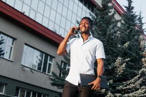 happy african american with a phone on the street photo