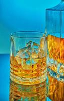 A glass and square crystal decanter with scotch whiskey or brandy photo