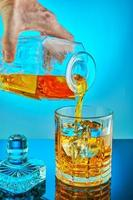 Pouring square crystal decanter with scotch tape whiskey or brandy photo