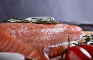 Raw salmon fillet pepper salt dill lemon rosemary and cherry photo