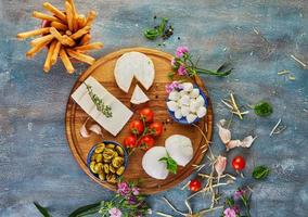 Cheeses of different shapes and tastes on a round wooden plate photo