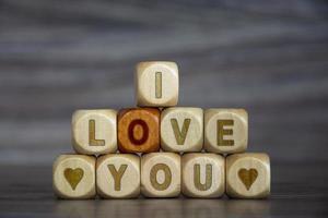 palabra te amo en cubos de madera sobre fondo borroso. declaración. foto