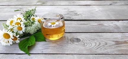 té de manzanilla y un ramo de manzanilla foto