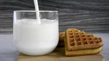 lait et biscuits avec un coeur. le lait est versé dans une tasse en verre. video