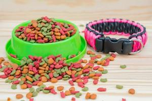 Pet food with dog collar on wooden background photo