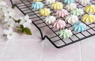 Multicolored meringue on a baking rack photo