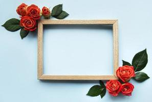 Flowers composition. Wooden frame and red  roses and leaves photo