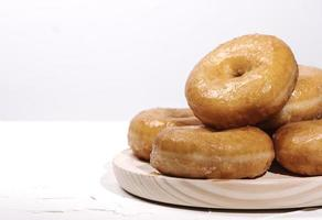 wooden tray with many doughnuts on a white background photo