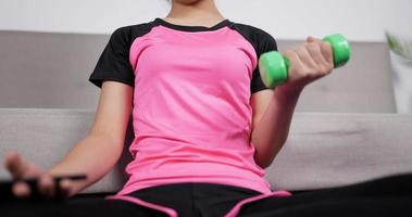Woman Holding Smartphone and Training Dumbbells video