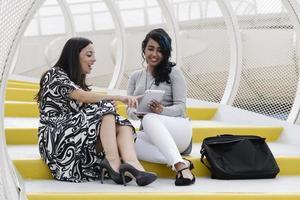 mujeres de negocios mirando una tableta y teniendo una conversación foto