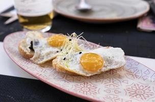 Plato de huevos fritos sobre mini tostadas crujientes con trufa foto