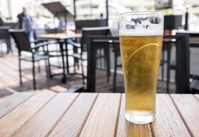Vaso de cerveza fría con espuma sobre una mesa de madera foto