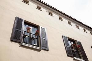 Fachada de pared con dos balcones de madera y macetas con flores rojas foto