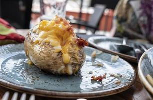 Roasted potato on blue plate stuffed with cheddar cheese and bacon photo