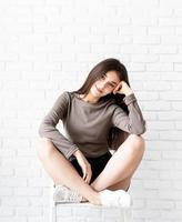 Mujer con cabello largo sentado sobre fondo de pared de ladrillo blanco foto