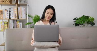 femme travaillant sur un ordinateur portable sur le canapé video