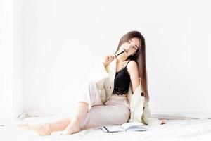 Mujer en ropa de casa cómoda escribiendo notas sentado en el suelo foto