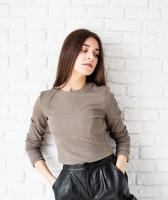 woman on white brick wall background holding hands in pockets photo