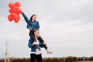 young loving couple with red balloons embracing outdoors having fun photo