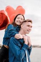 Joven pareja amorosa con globos rojos abrazando al aire libre foto