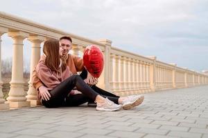 Pareja abrazándose al aire libre en el parque sosteniendo globos foto
