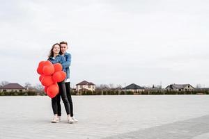 Joven pareja amorosa con globos rojos abrazándose y besándose al aire libre foto