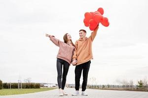 Joven pareja amorosa con globos rojos abrazando al aire libre divirtiéndose foto