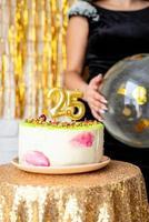 Velas de oro 25 en tarta de cumpleaños sobre fondo dorado brillo foto