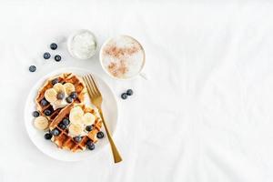Vista superior de gofres recién hechos con arándanos, plátano y yogur foto